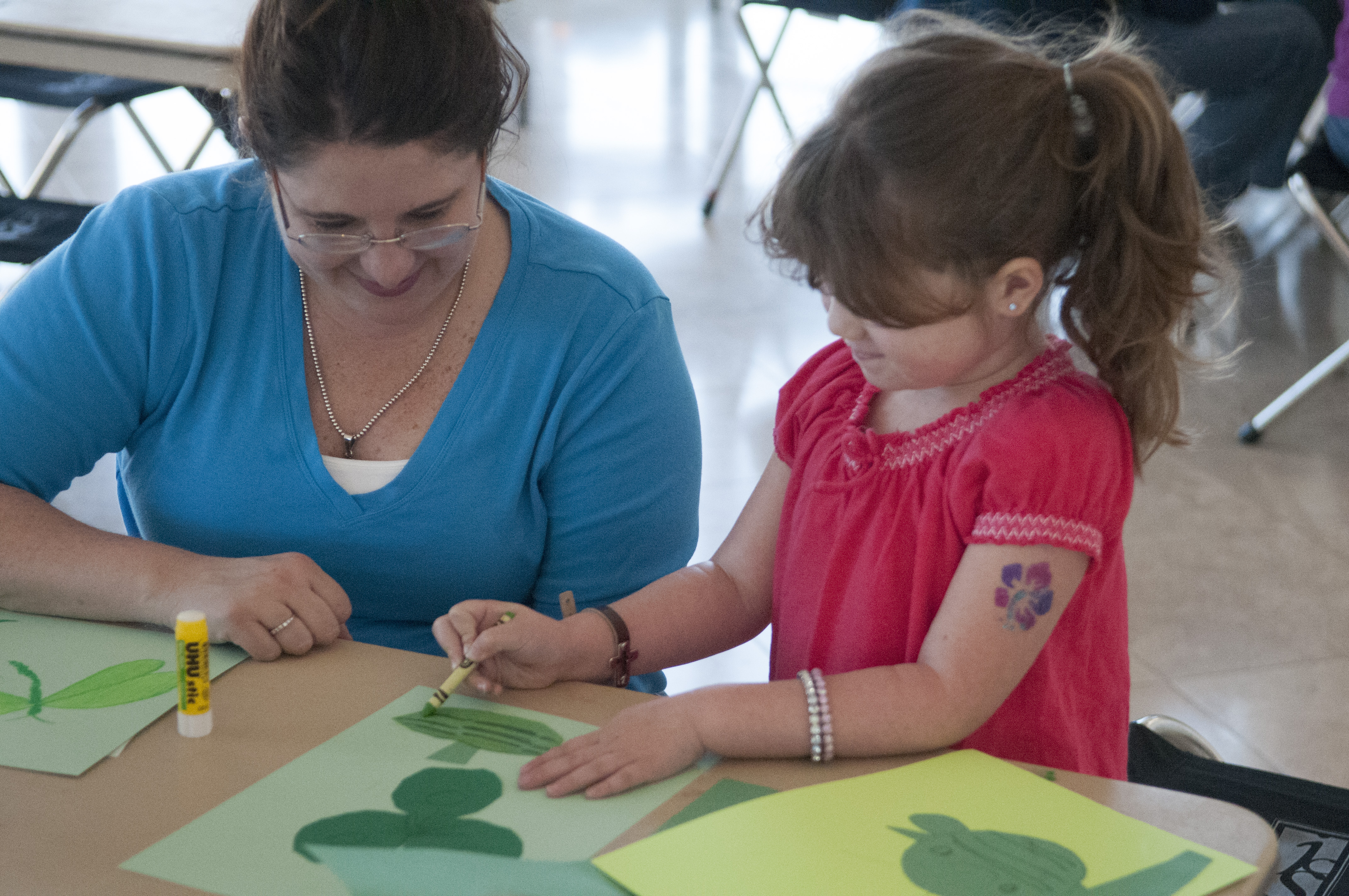 Woman works on an art project with a child.