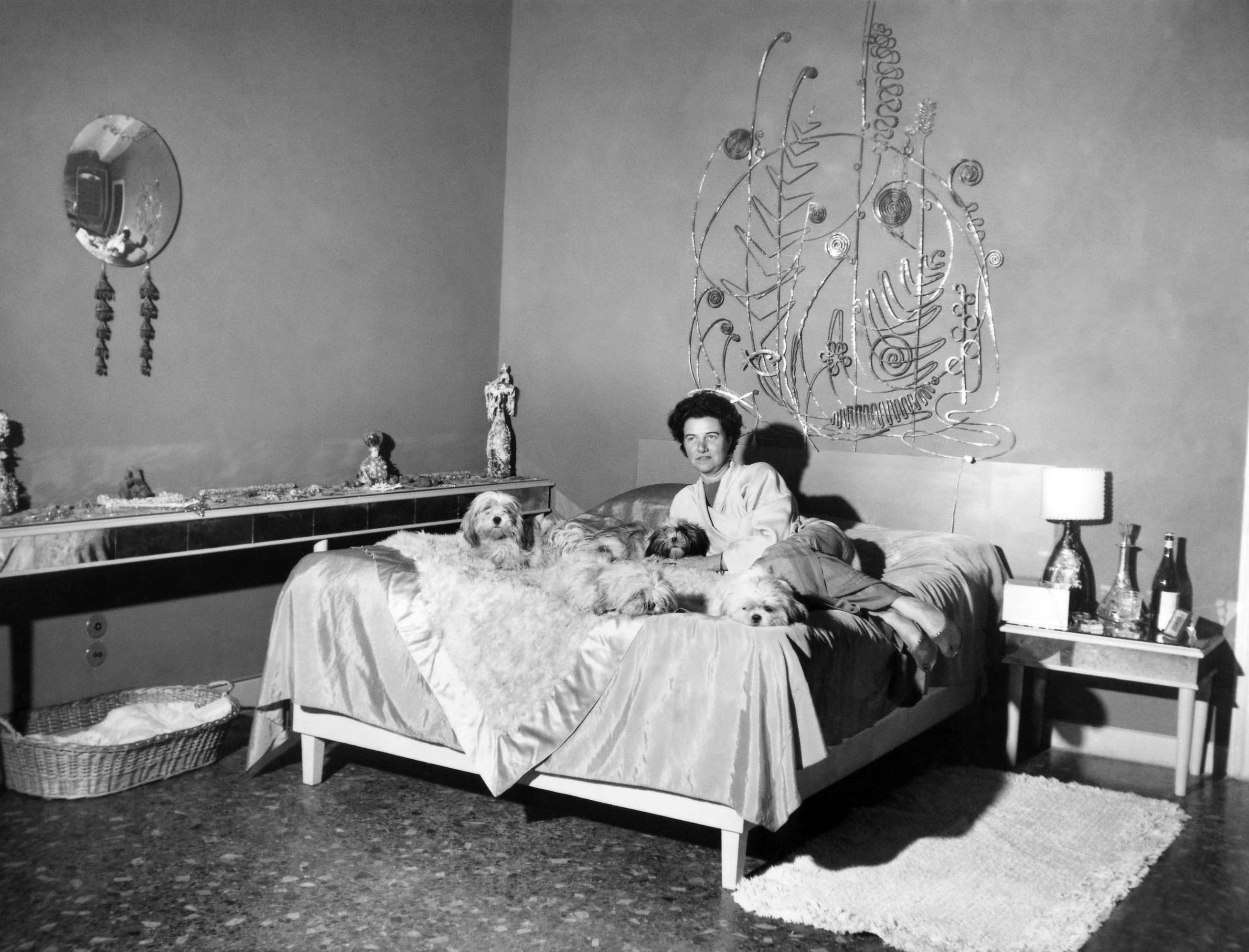 Peggy Guggenheim seated on a bed with a dog.