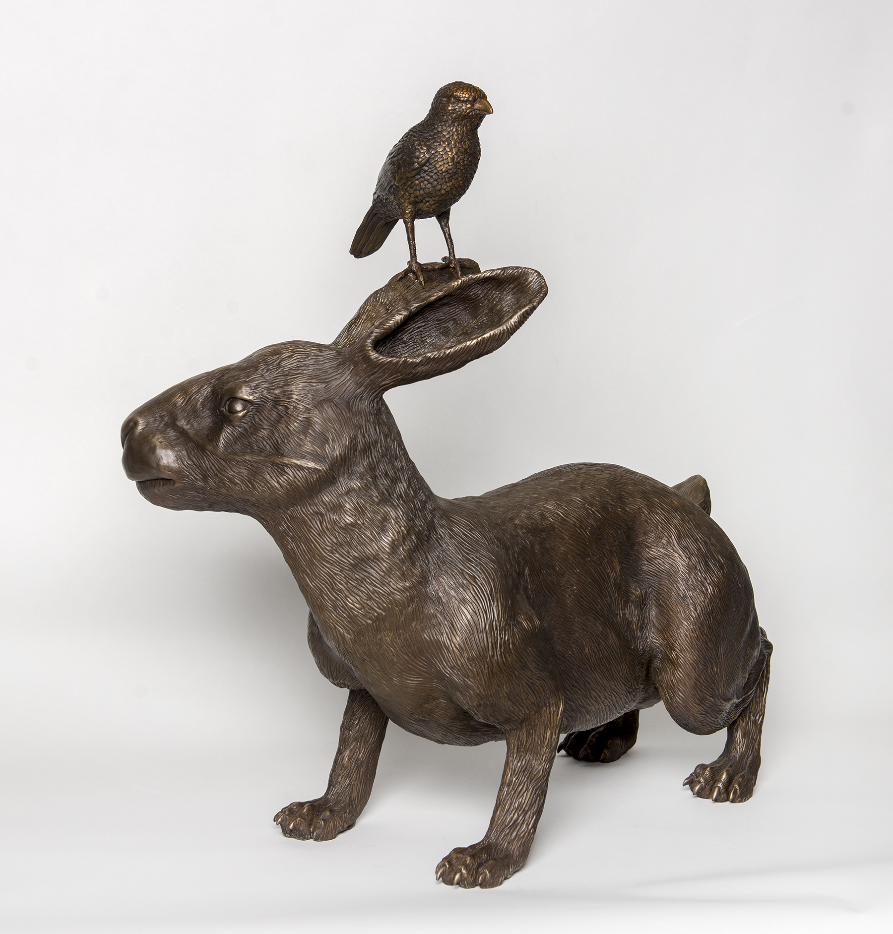 Profile of rabbit sculpture with a bird on its head.