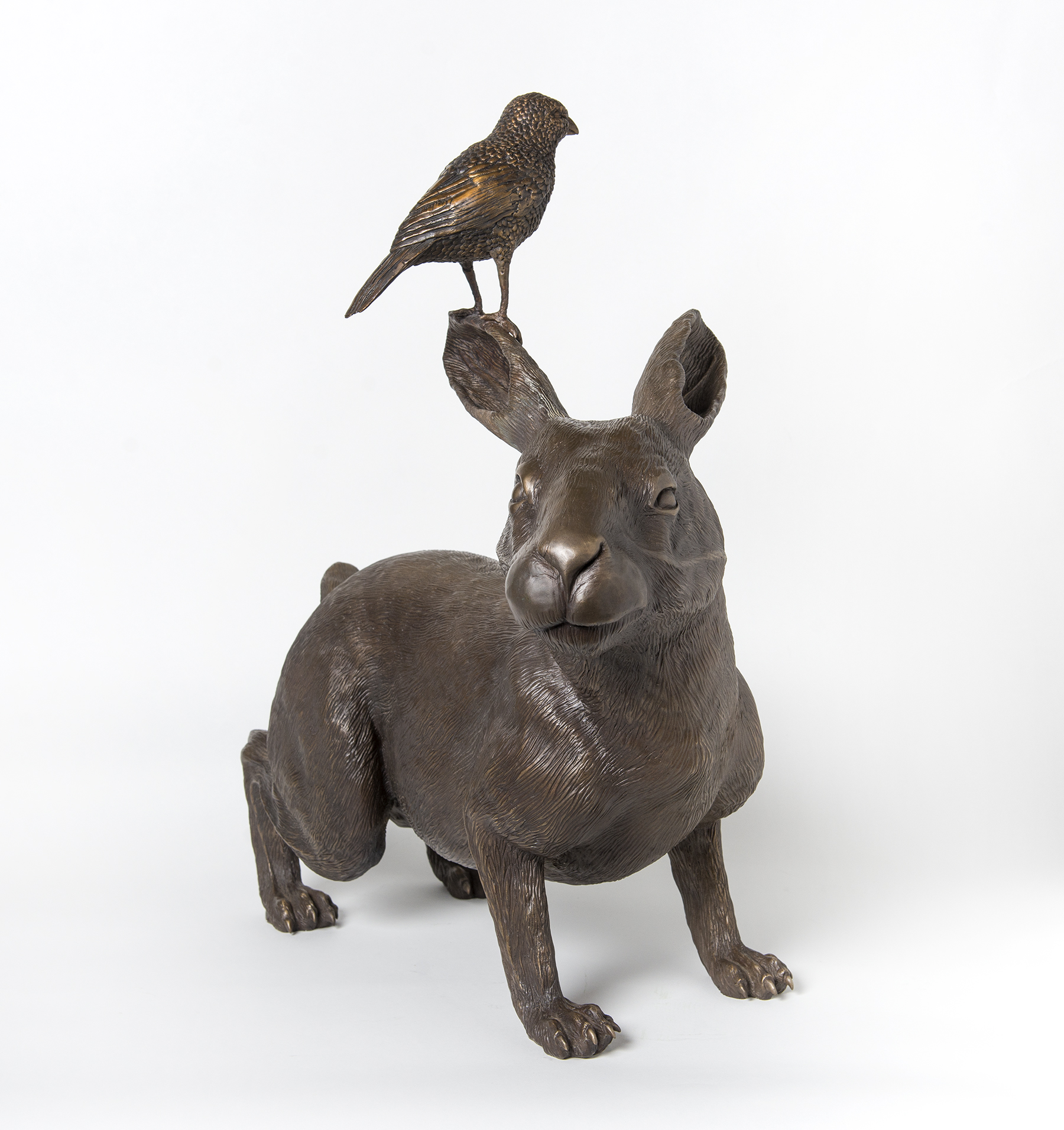 Forward-facing bronze rabbit sculpture with bird