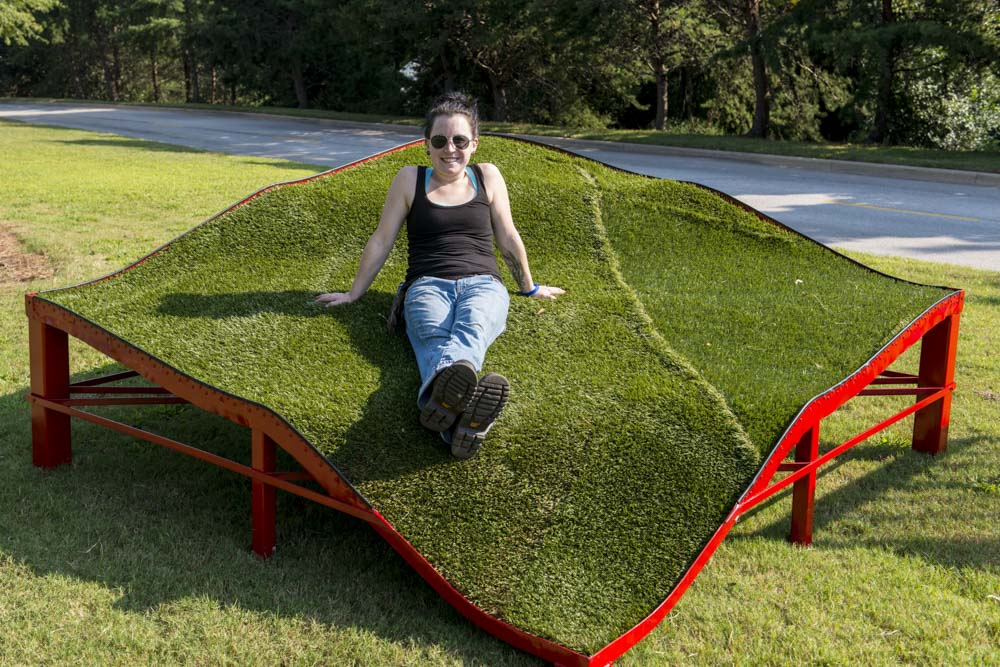 Stacey Rathert of Mississippi poses with her work You Are Here, 2013 Steel, artificial turf, and ground cover