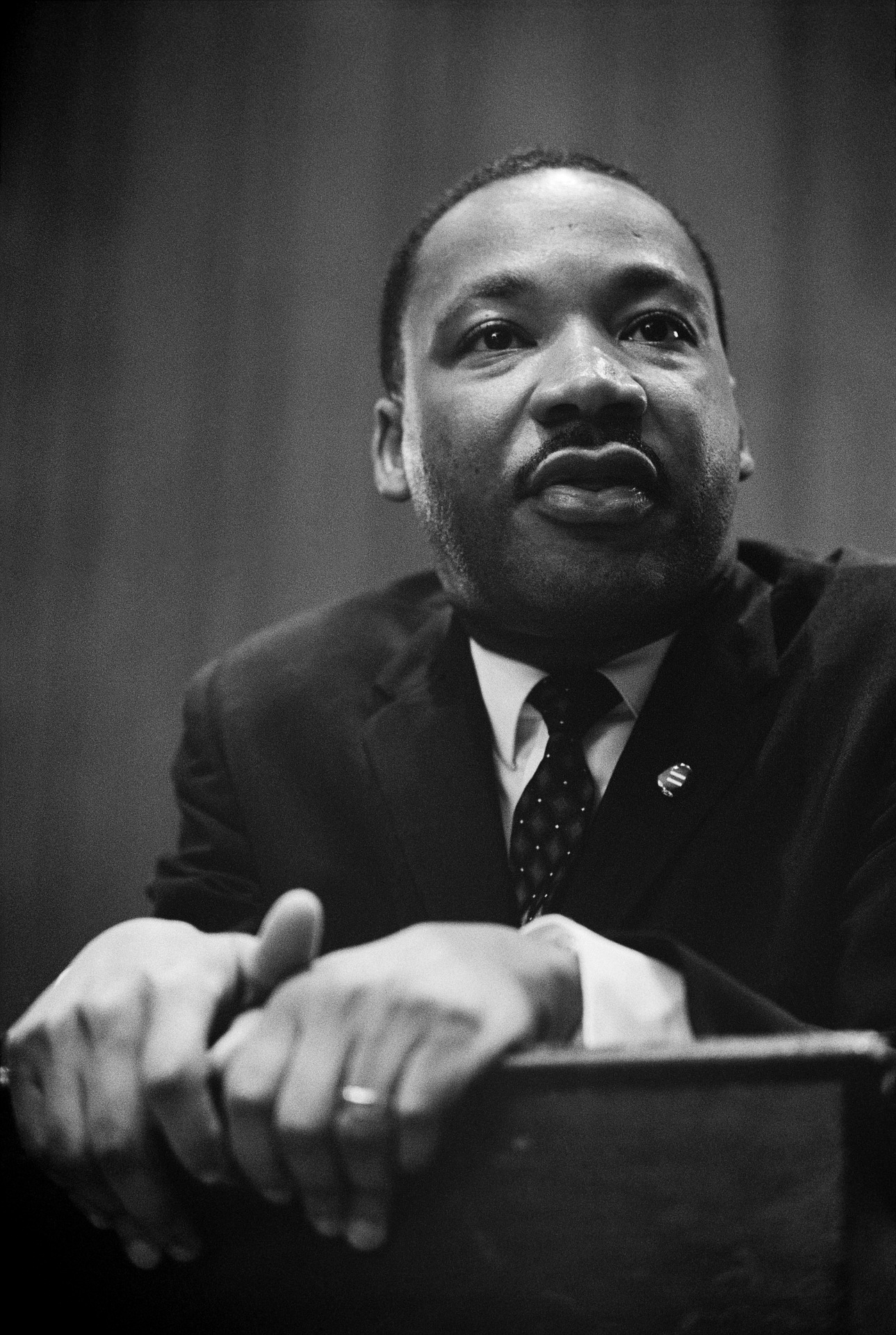 Rev. Dr. Martin Luther King stands at a lectern.
