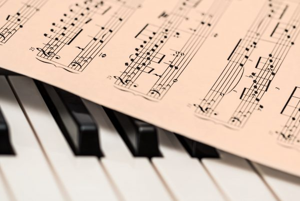 Close up of sheet music on top of piano keys.