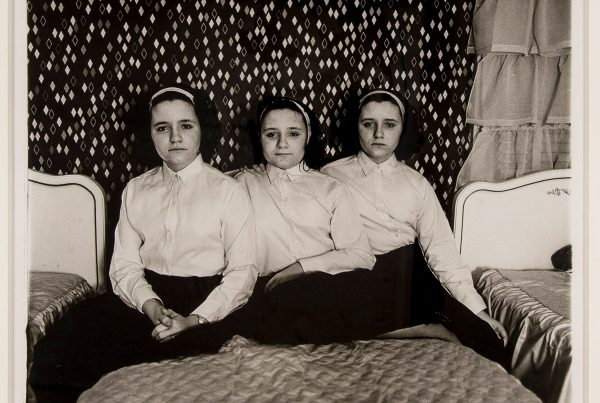Three girls sit on a bed in a silver gelatin print.