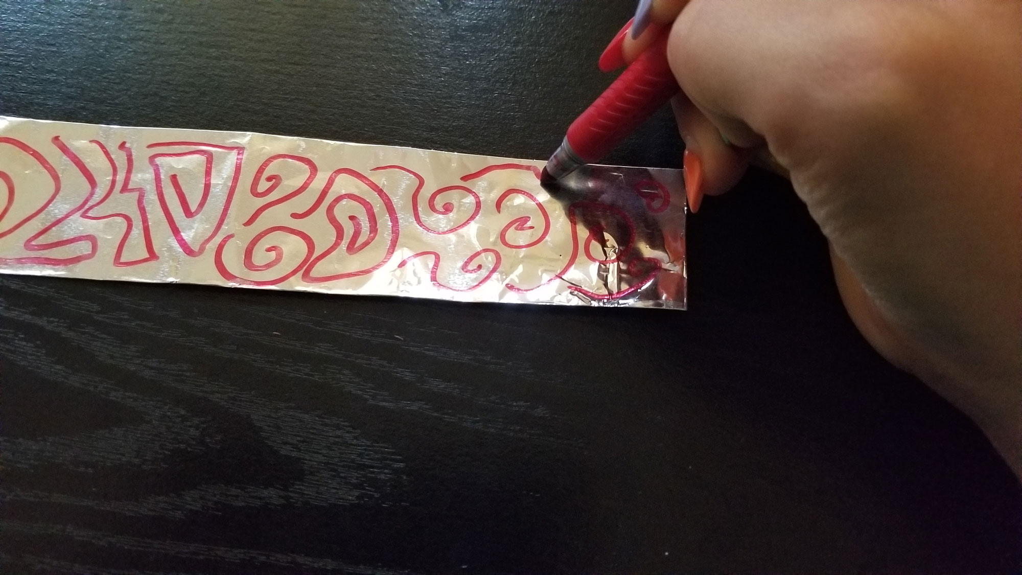 Draw a variety of abstract shapes on aluminum foil to create a pattern.