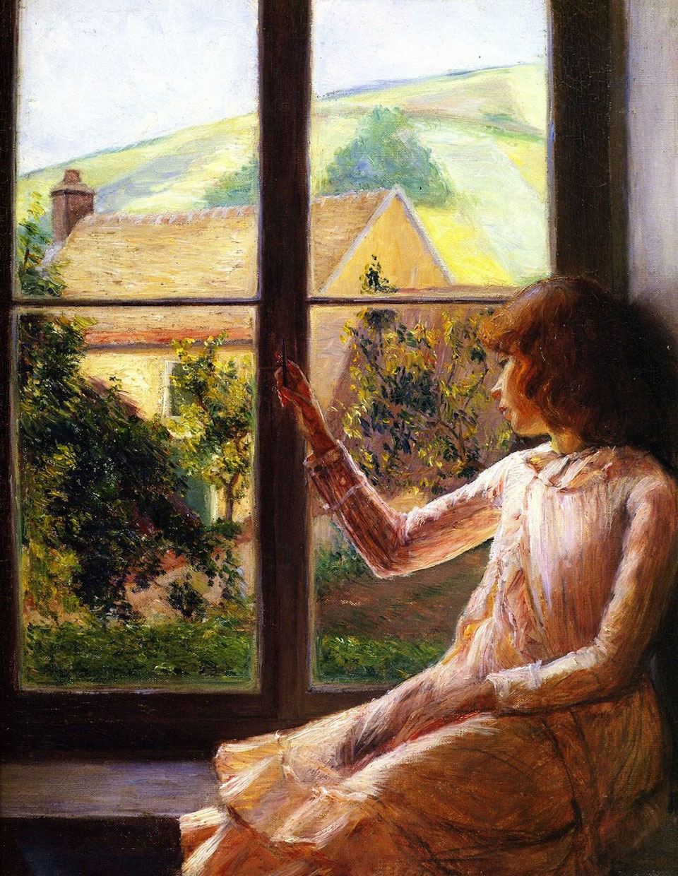 A young girl looks out of a window.