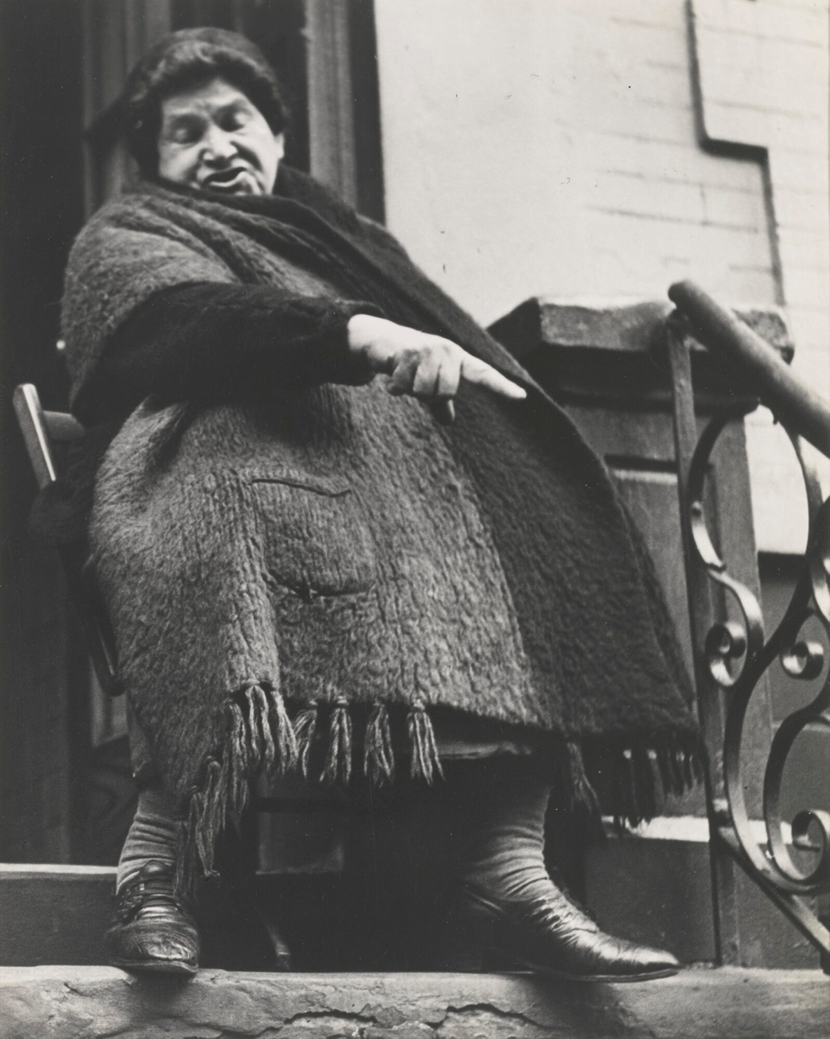 A woman sitting on a stoop gestures in this black and white photograph.