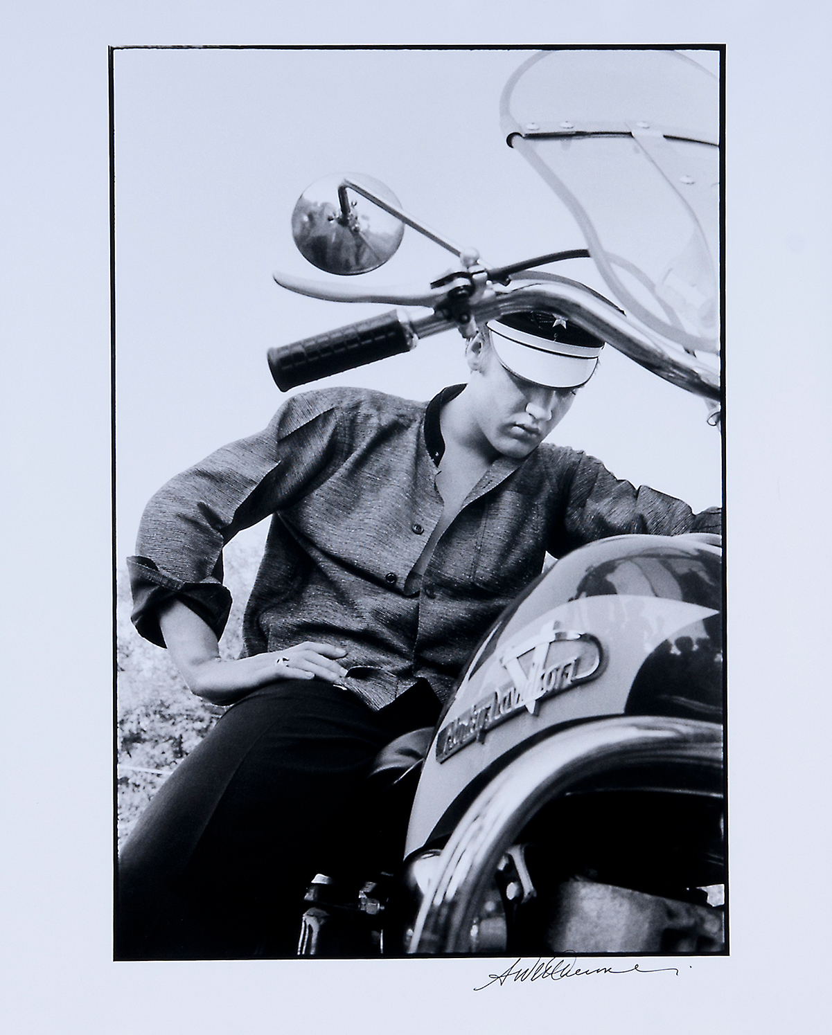 Musician Elvis Presley sits on a motorcycle.
