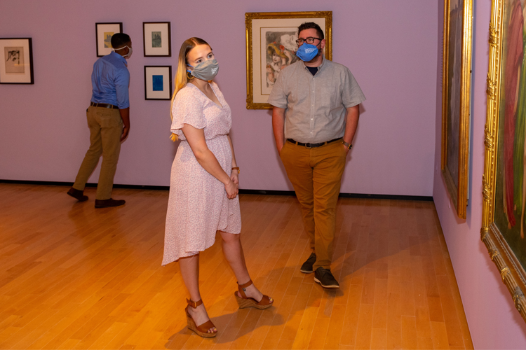 A group of students, wearing masks, view art in a gallery.