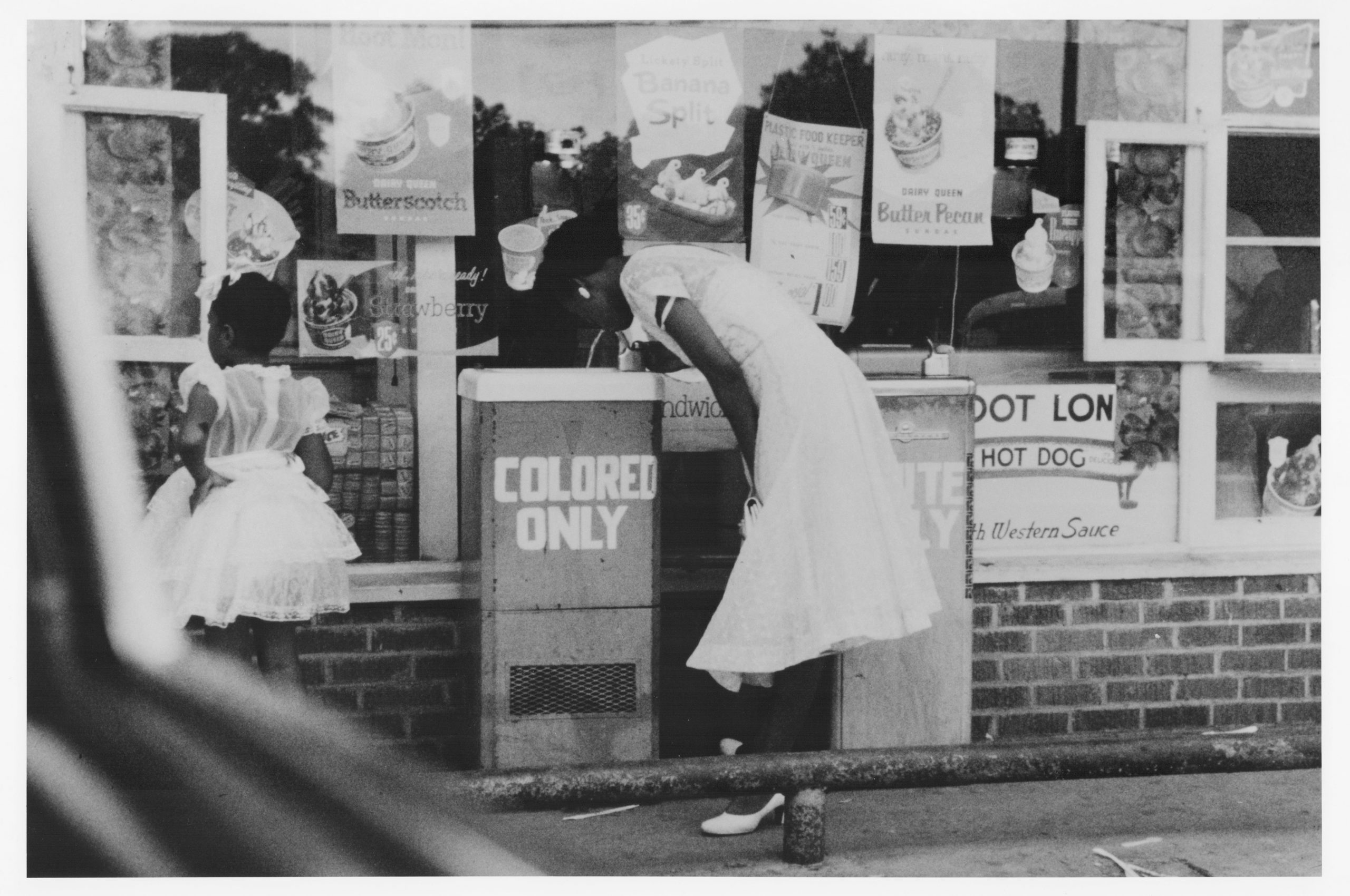 "A woman takes a drink from a water fountain labeled ""colored only."""