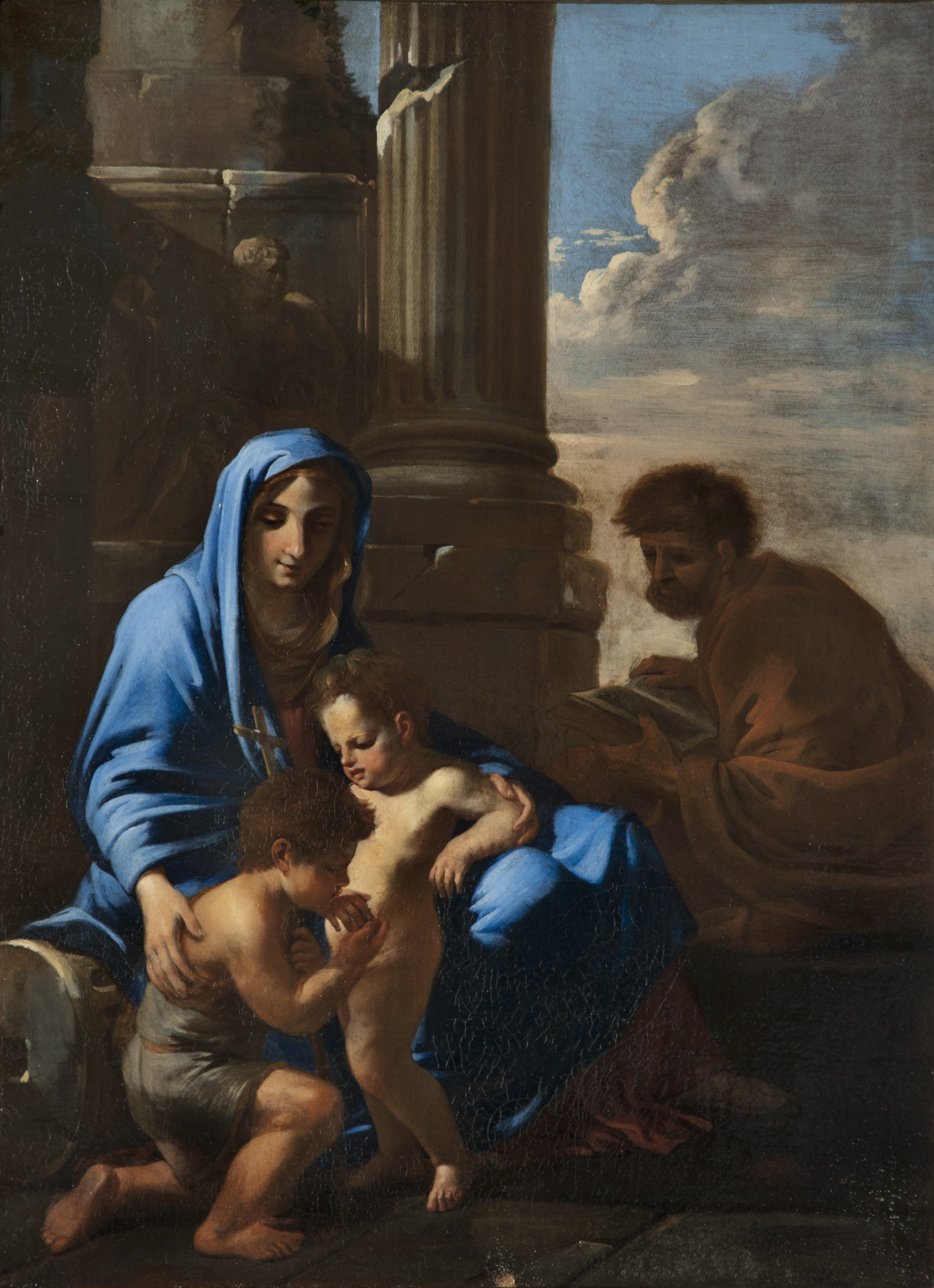 A mother holds two young children, while a man looks on