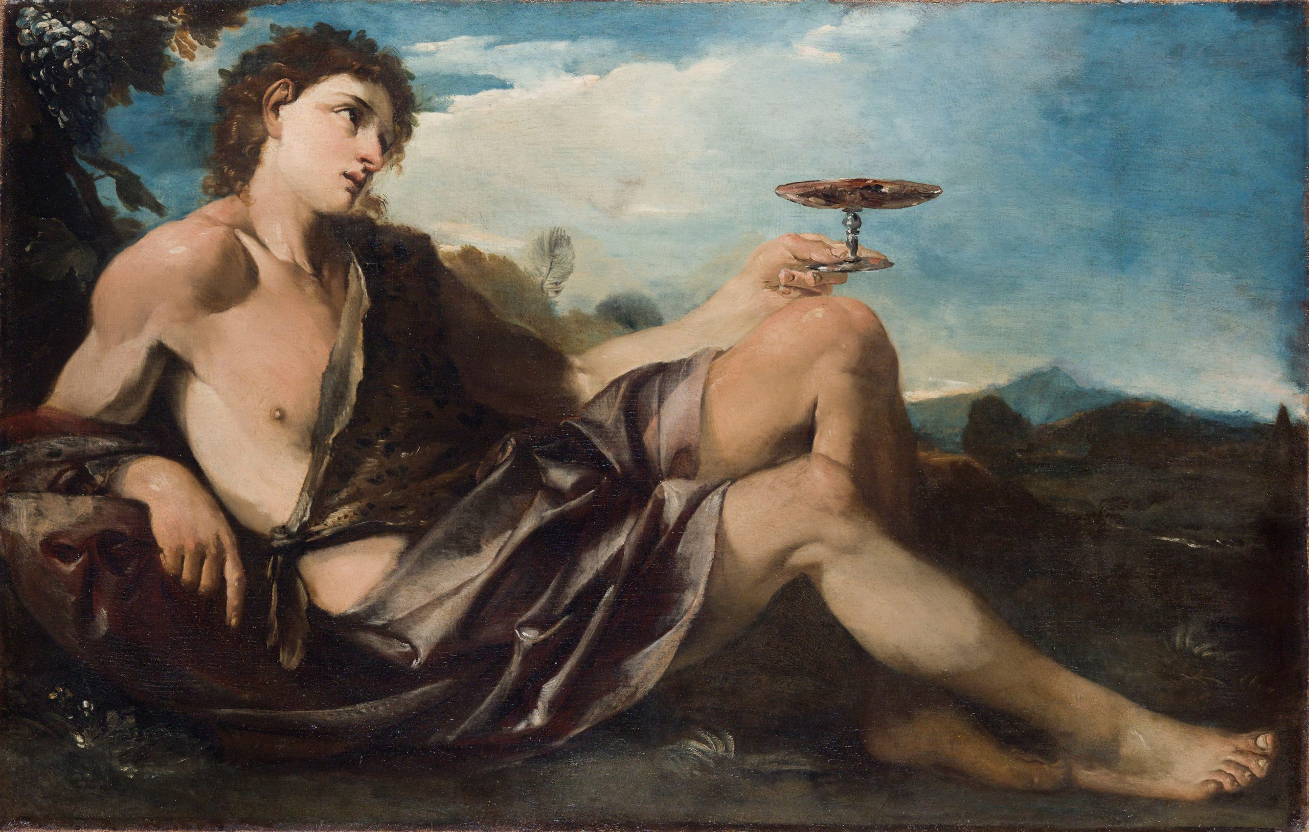 A handsome young man, wearing a toga, reclines and holds a cup