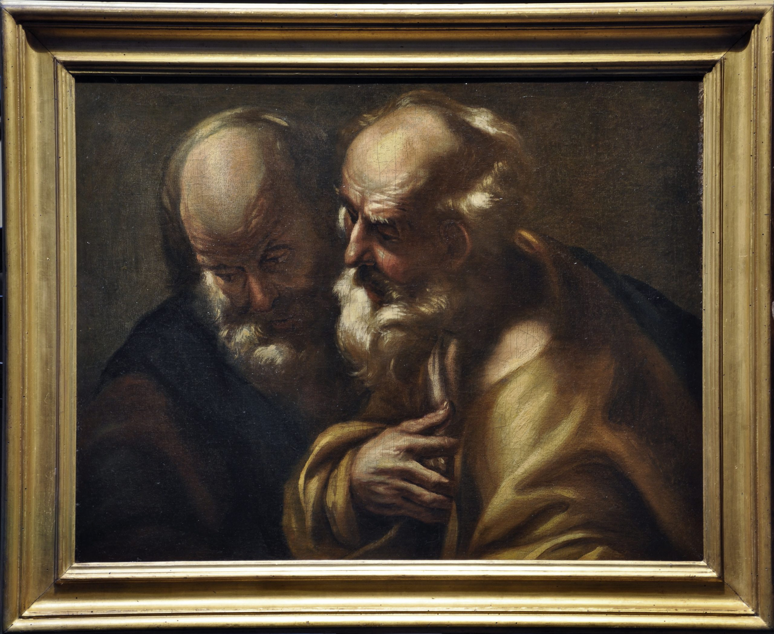 Two men lean in close to one another as if they are whispering.