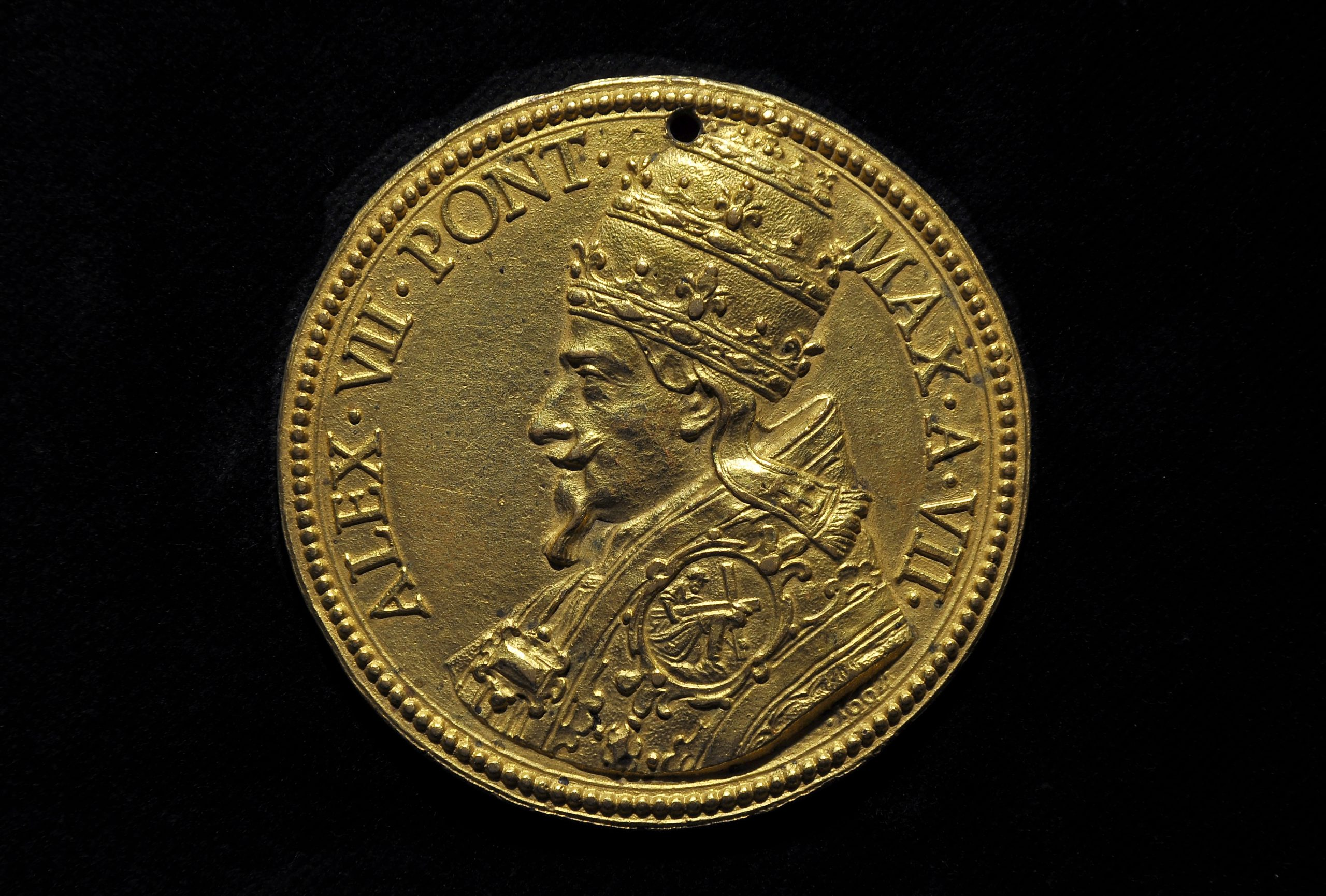 A 17th-century papal figure, in profile, adorns a gold coin.