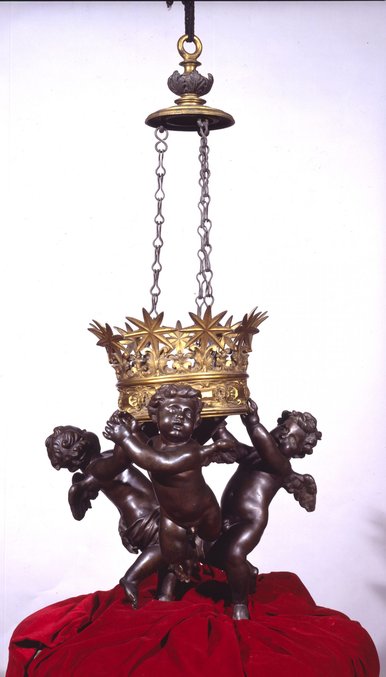 Sculptures of three winged cherubs hang from a light fixture adorned with five-pointed stars