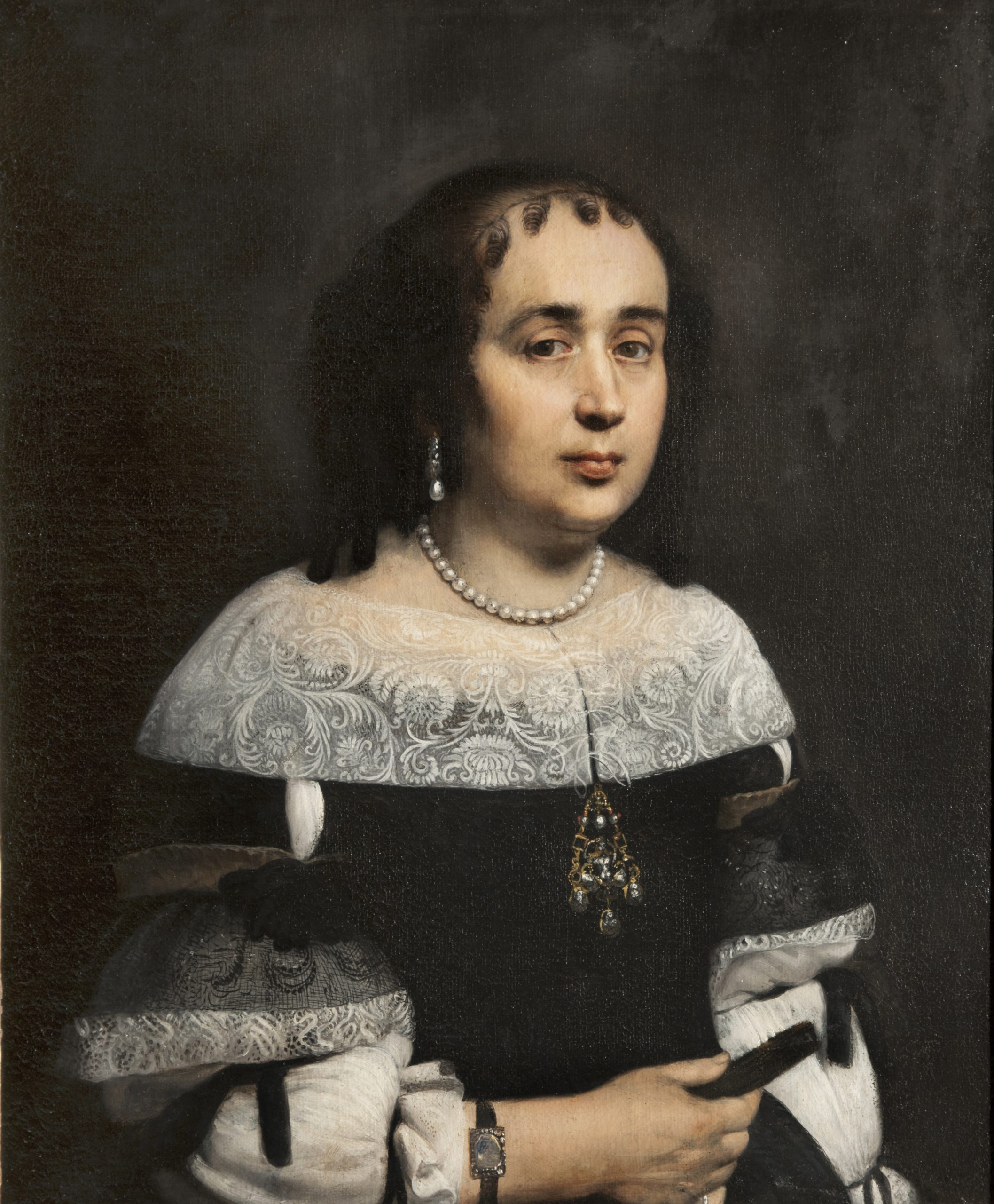 A woman wearing pearls and a dark gown