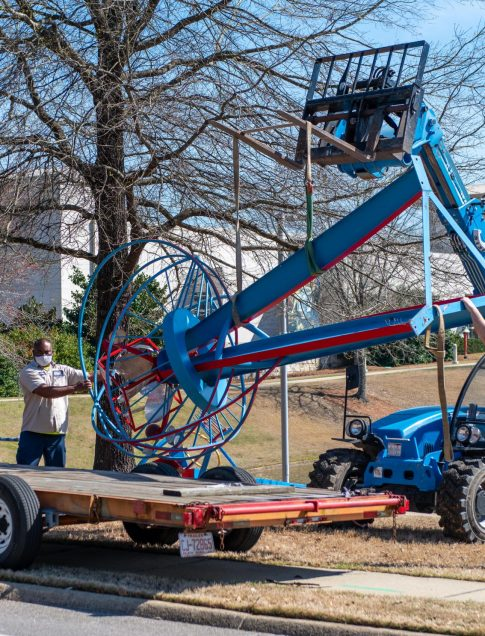 A construction crane lowers a sculpture on to a truck bed.