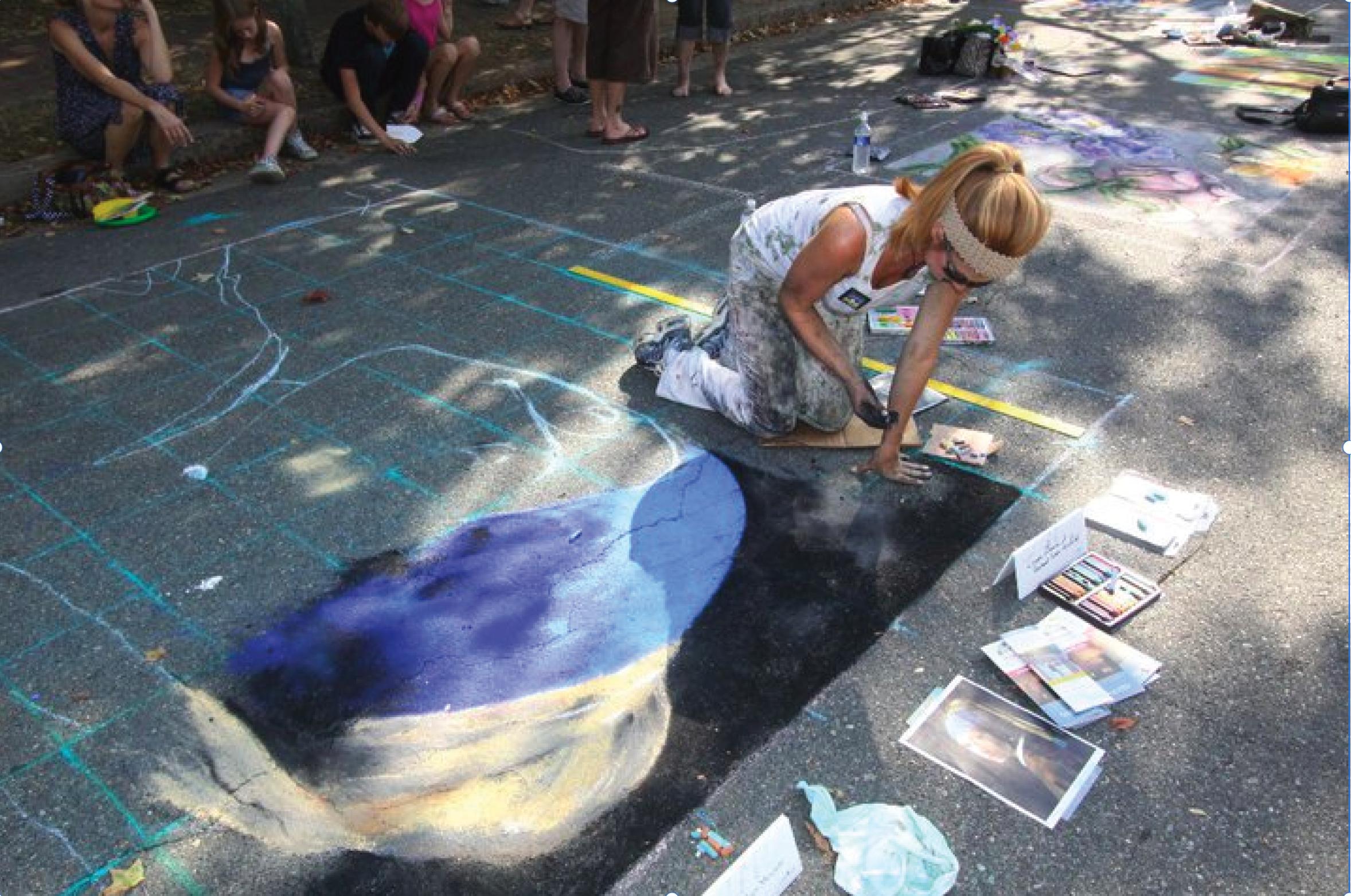 An artist recreates a painting on the street