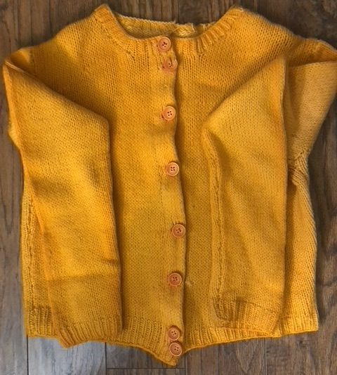 A soft handmade sweater in a warm and cheery yellow.