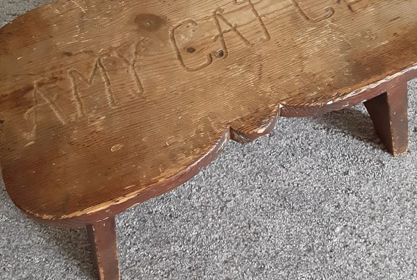 A rough and well-loved wooden footstool with the name Amy Cates carved on the top.