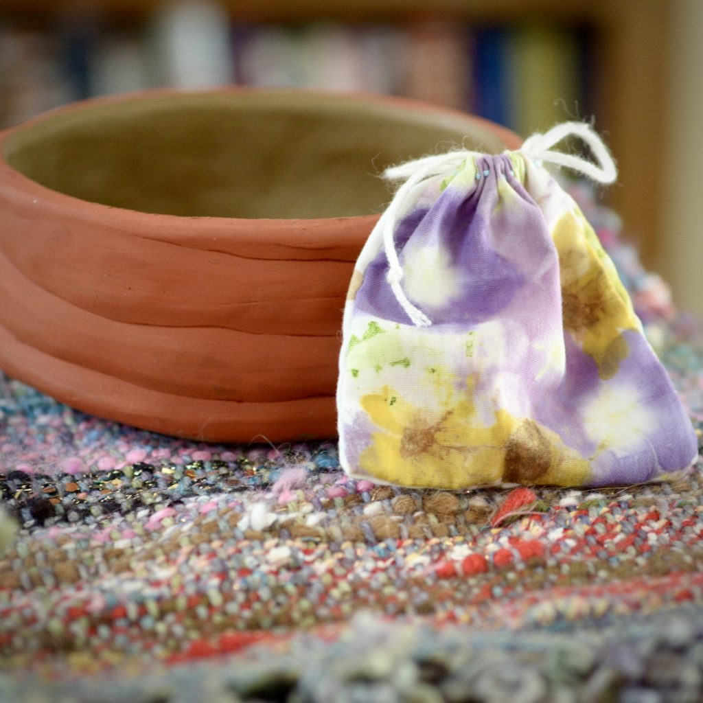 A small bag placed against a handmade coiled pot.