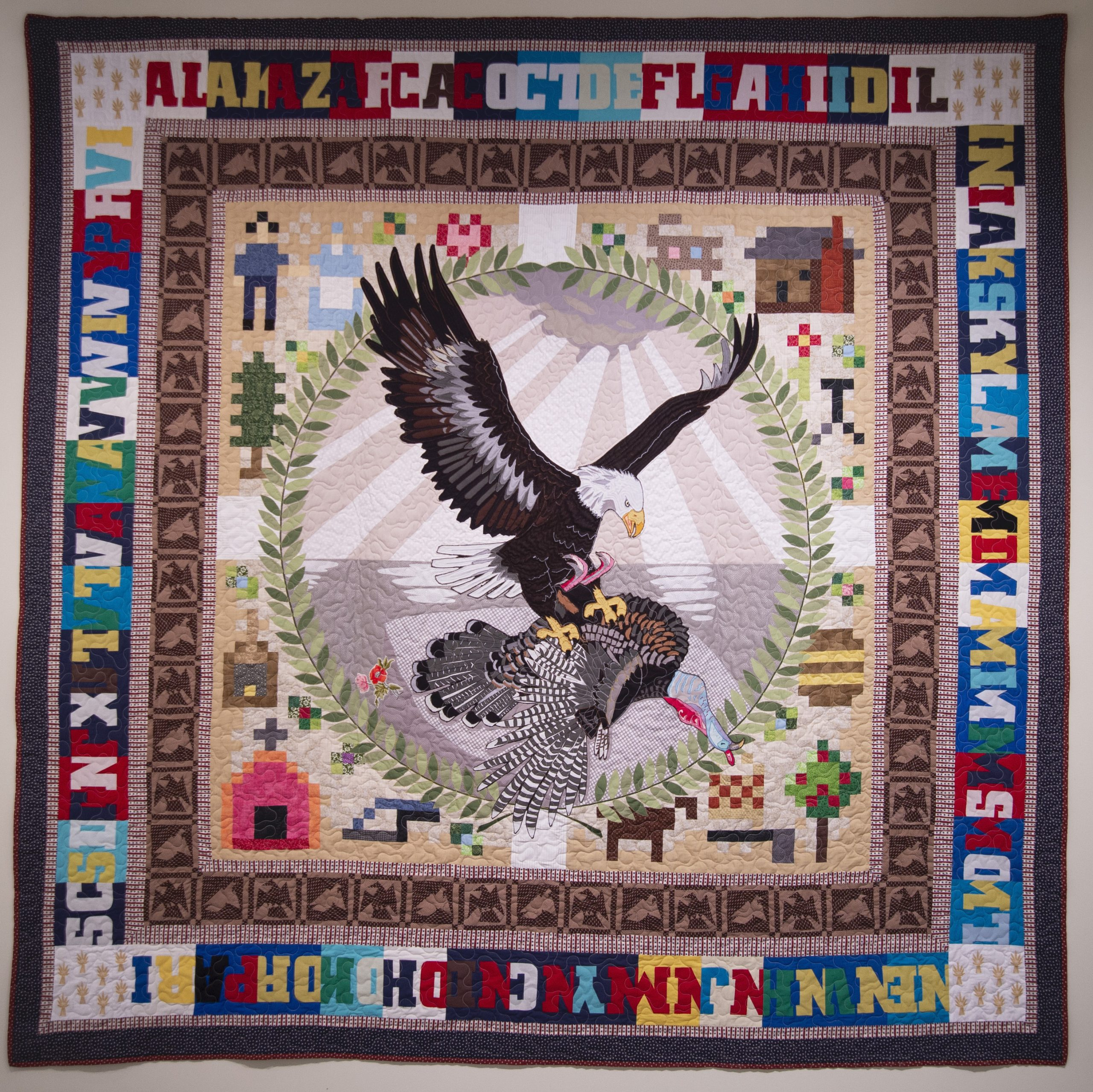 A Bicentennial quilt, featuring an eagle attacking a wild turkey, surrounded by a border of state abbreviations.