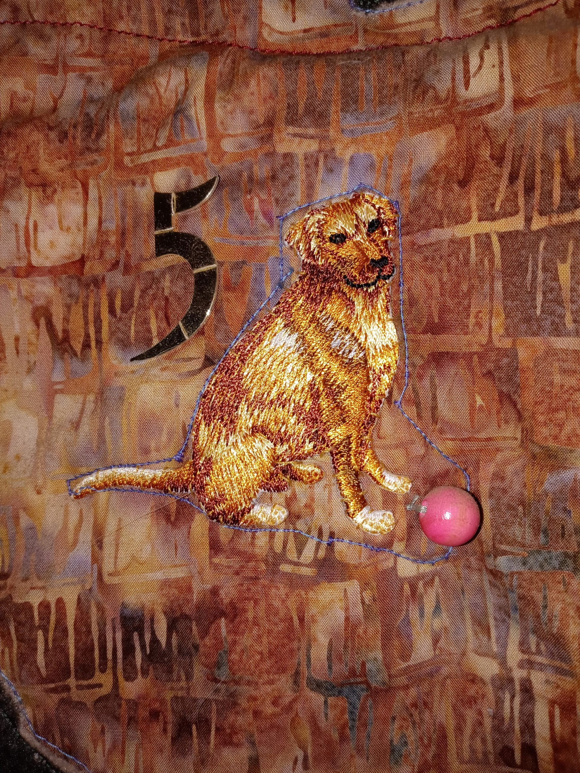 An embroidered dog with a rubber ball and a number 5 from a clock.