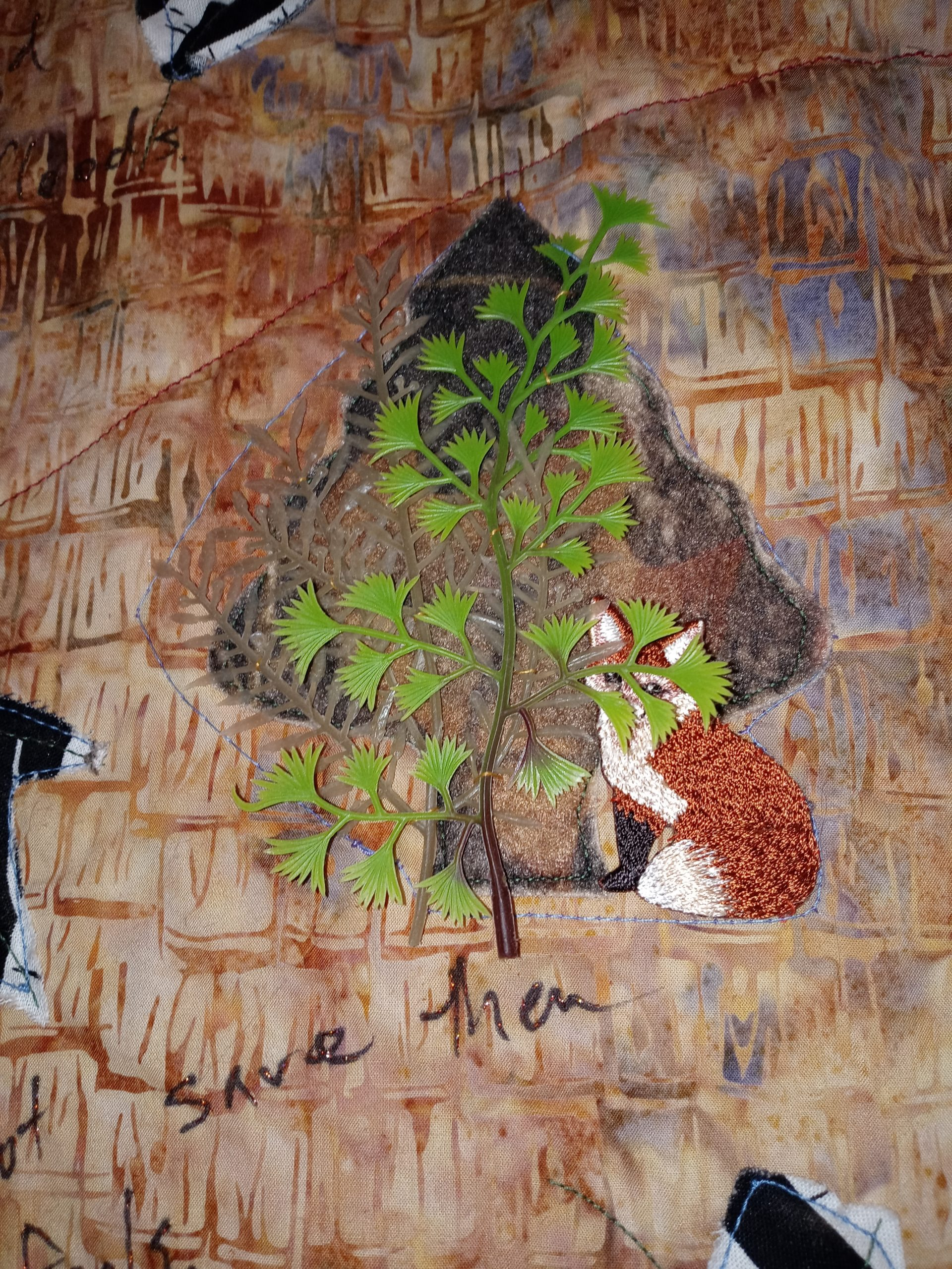 An embroidered fox hides behind a plastic toy tree on a quilt.