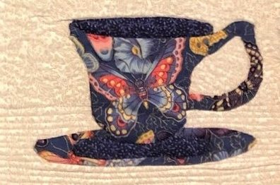 A quilted teapot with a warm and cool colored butterfly.