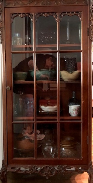 A wooden china cabinet filled with delicate teacups.
