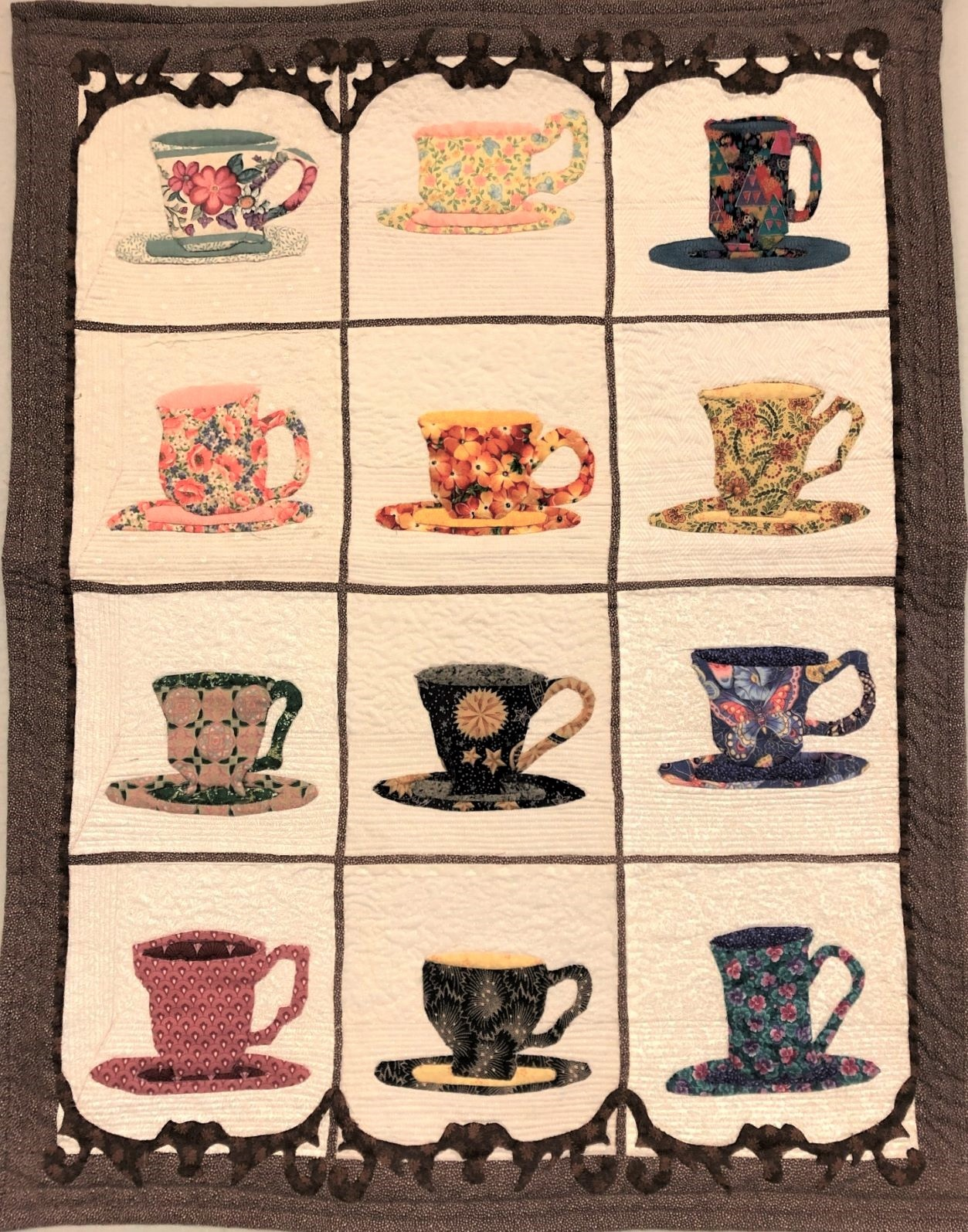 A quilt with floral teacups.