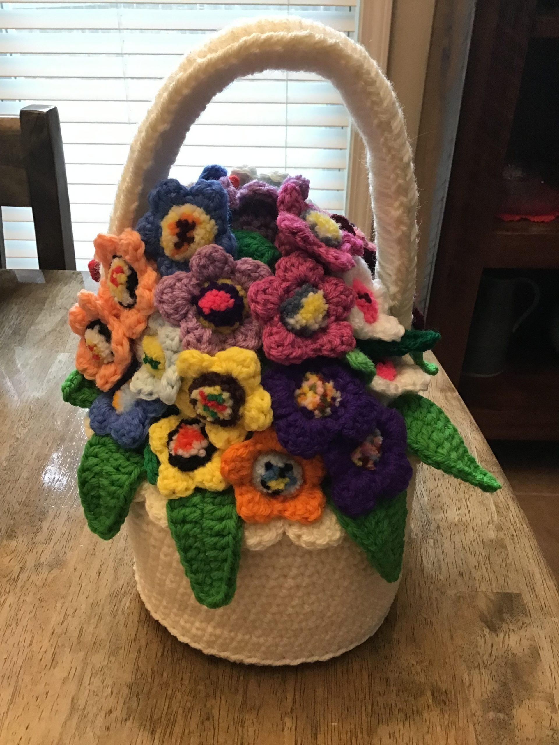 A basket and flowers made from yarn.