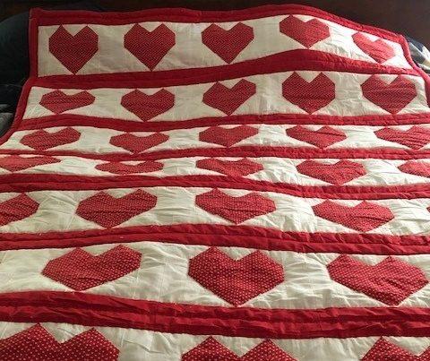 A handmade quilt with heart design