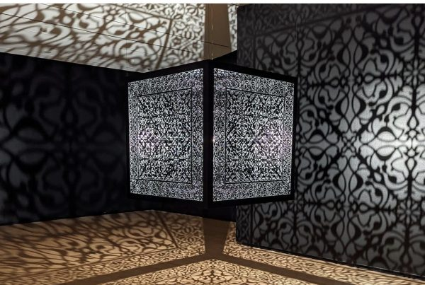 A large metal cube suspended from the ceiling, casting a cool complex pattern.