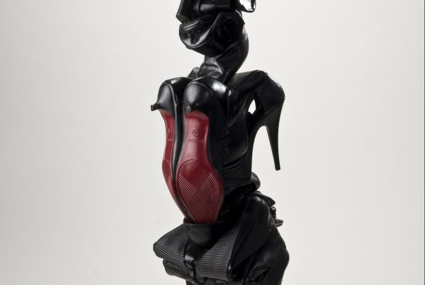 A sculpture made of shoes that resembles a woman's form