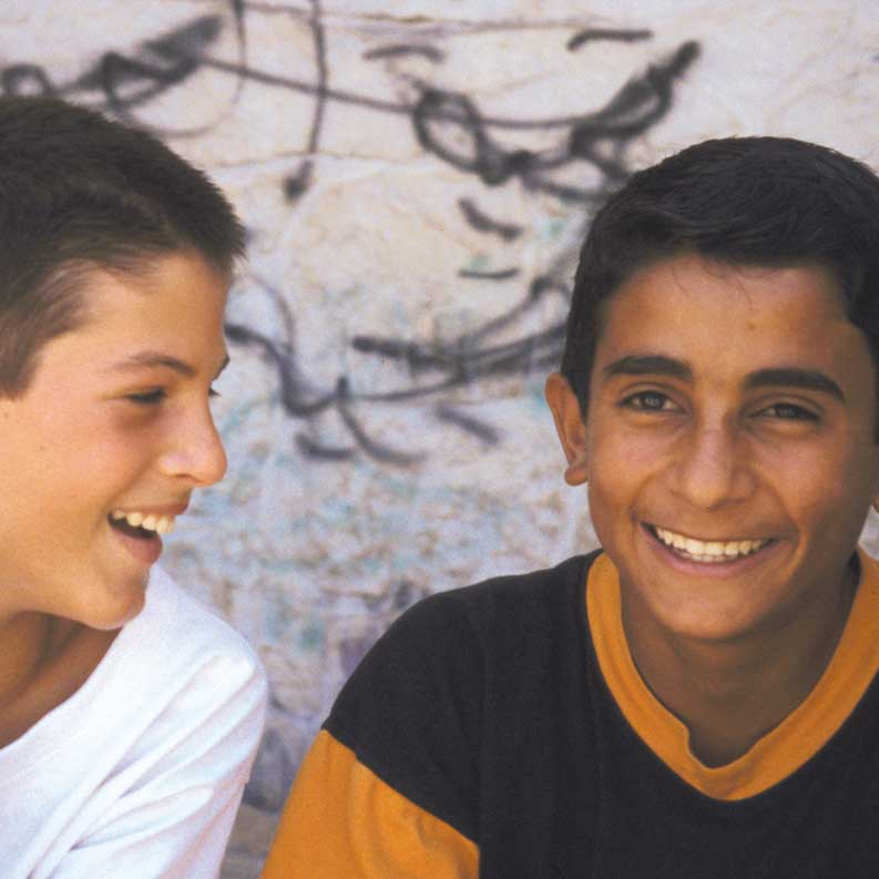 Two boys laughing in a film still from