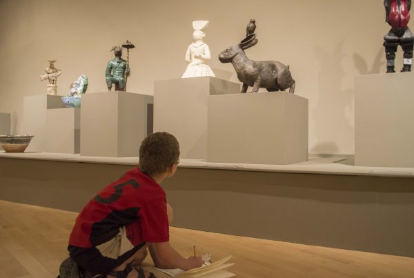 Boy sketches a sculpture in the gallery.