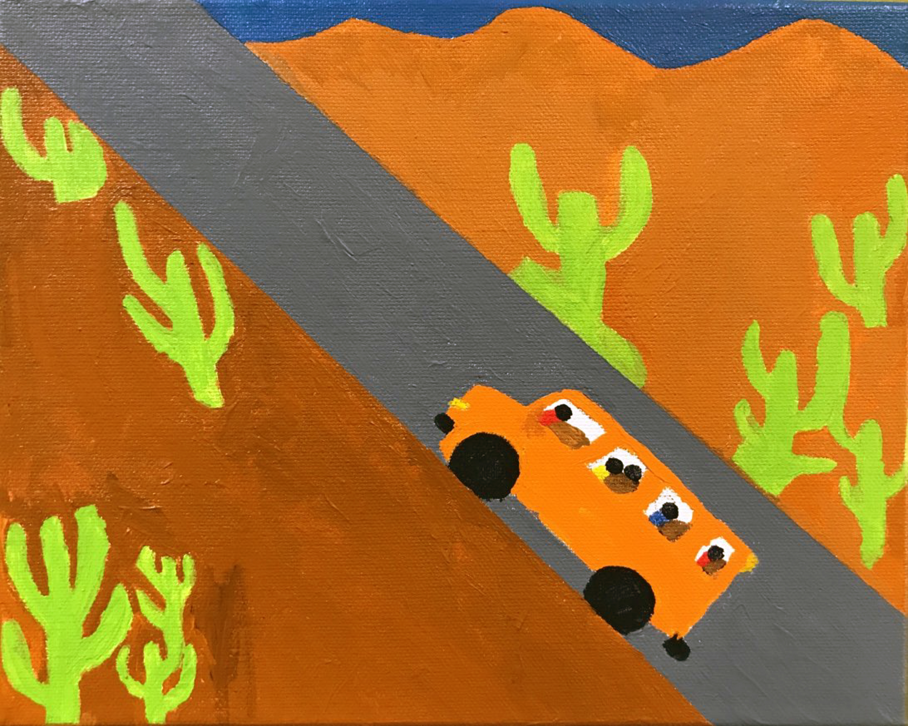 A bus drives on a road in the desert with mountains and cacti on either side of the road.