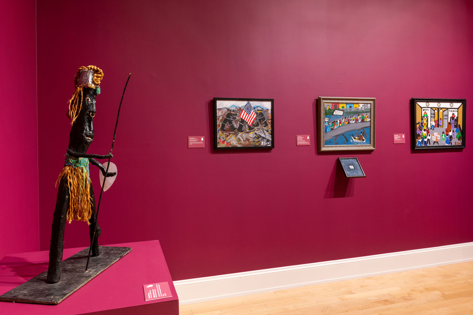 African-inspired statue amidst folk art paintings.