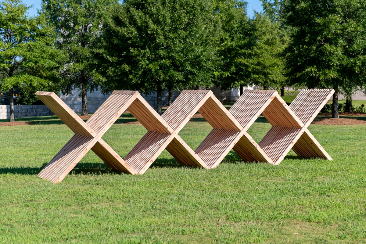A sculpture constructed from wood beams, forming multiple X shapes.