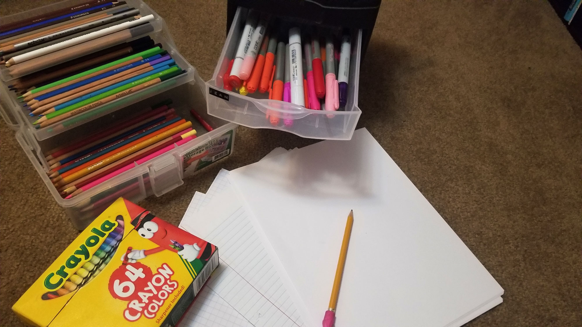 Paper, pencil and markers on display for an art project.