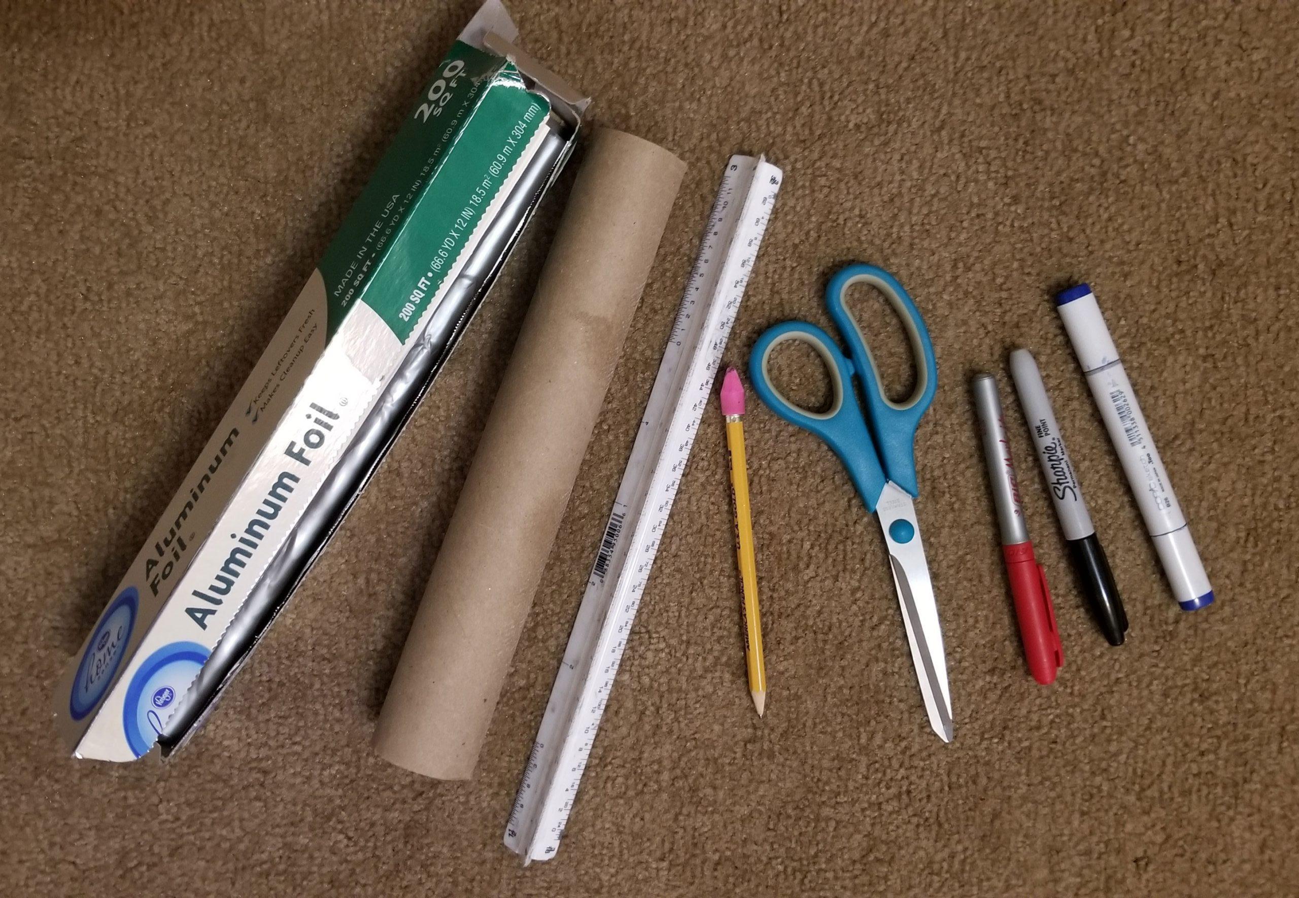 Art project materials, including scissors, pencil and foil.