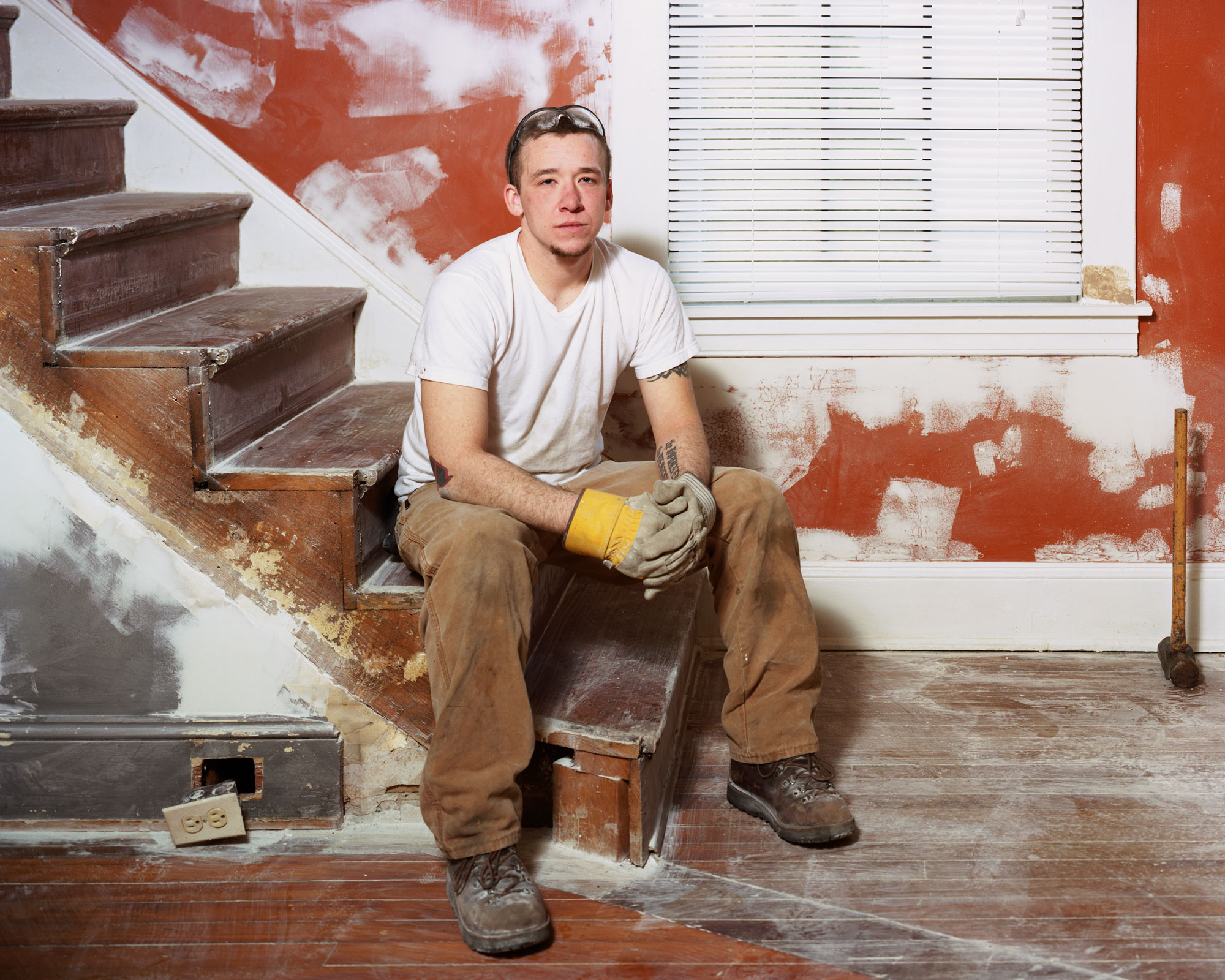 A construction worker sits on unfinished stairs.