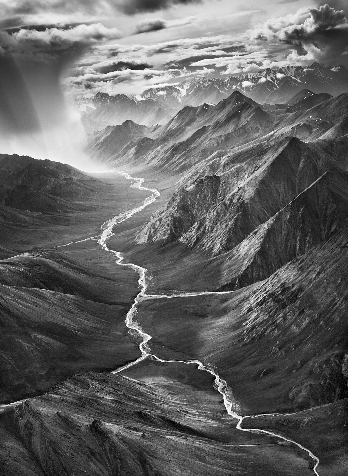 A photograph of a mountain range and rivers in Alaska.