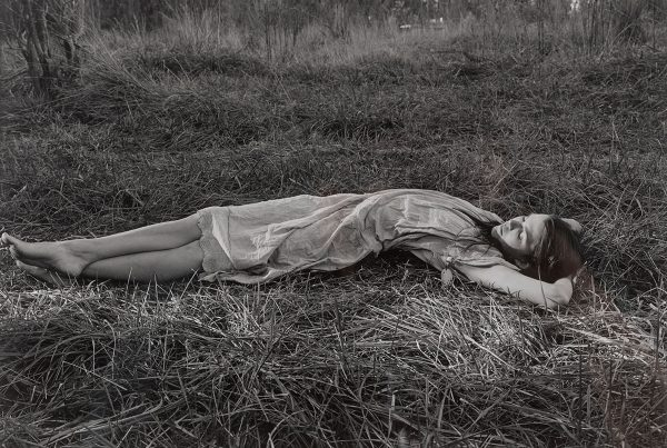 A photograph of a woman lying in the grass.