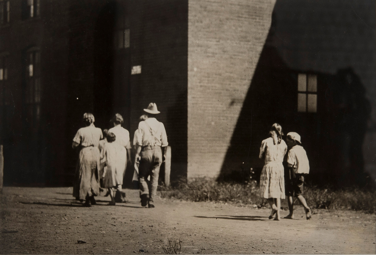 A photograph of factory workers entering a job site.