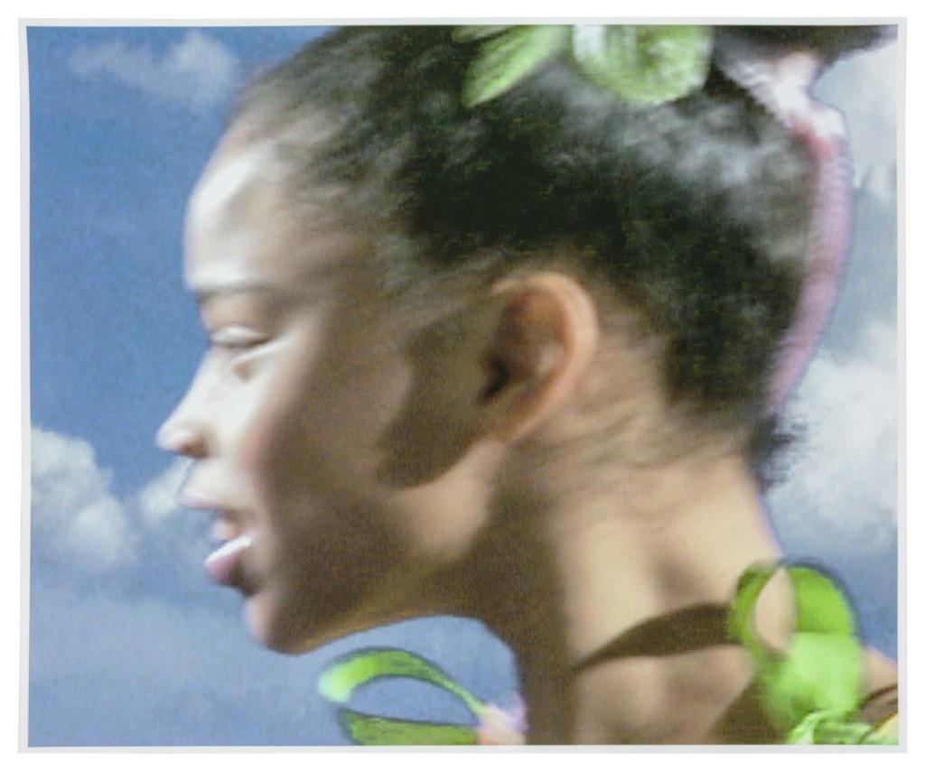 A Black dancer, in profile, smiles.