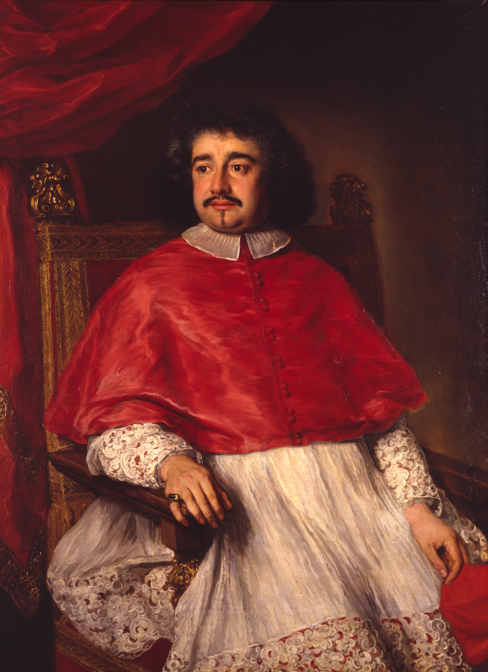 A Catholic cardinal reclines in an ornate chair.