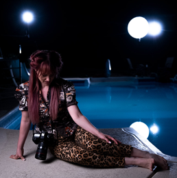 A woman sits in front of a pool staged for a night photoshoot, looking down at her camera.