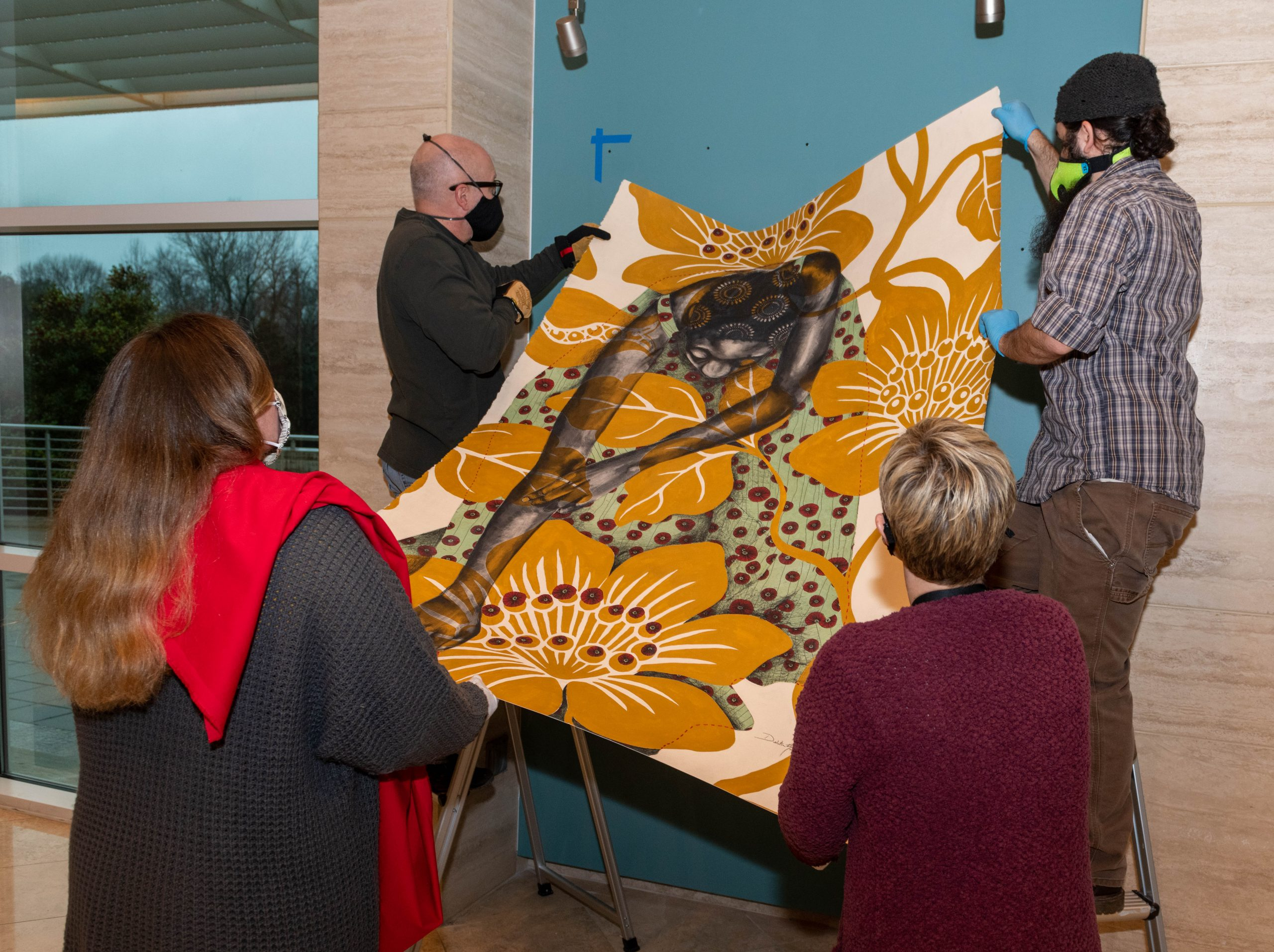 Museum staff install an artwork.